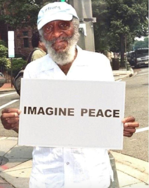 DICK GREGORY, HOLDING A PEACE SIGN