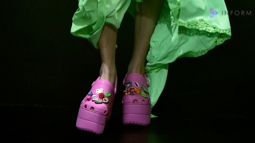 BALENCIAGA MODEL WEARING PINK CROCS ON THE RUNWAY IN A GREEN DRESS .png