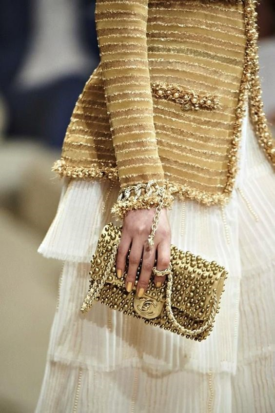 CHANEL COUTURE IN GOLD BLAZER AND GOLD BAG WITH A WHITE DRESS