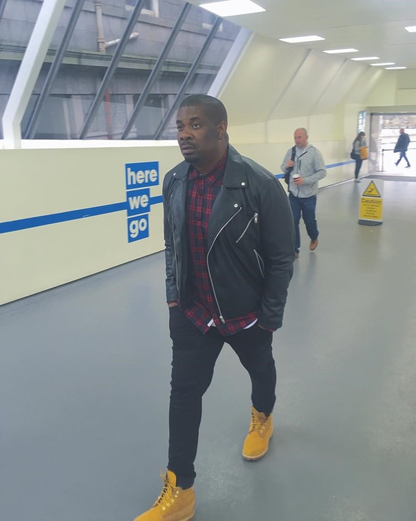 NIGERIAN MALE ARTIST DON JAZZY WALKING THROUGH AN AIRPORT PHOTO.png